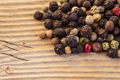 Dry  peppercorn mix on wooden background Royalty Free Stock Images