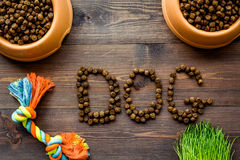 Dry pet - dog food in bowl with dog text on wooden background top view Royalty Free Stock Photography