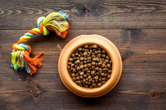 Dry pet - dog food in bowl on wooden background top view. Dry pet - dog food in plastic bowl on wooden table background top view Royalty Free Stock Photos