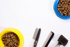 Dry pet food in bowl, combs and brushes for dogs on white background top view Stock Photos