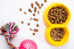 Dry pet food in bowl and toys for dogs on white background top view Stock Photo