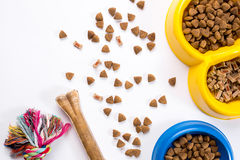 Dry pet food in bowl and toys for dogs on white background top view Royalty Free Stock Image