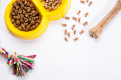 Dry pet food in bowl and toys for dogs on white background top view Royalty Free Stock Images