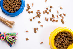 Dry pet food in bowl and toys for dogs on white background top view Royalty Free Stock Photography