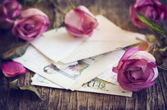 Dry Pink Roses and old Letter on Wooden Background Stock Photo