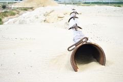 The dry pipe of the dredger lies on the sand in the sand quarry Royalty Free Stock Photography