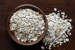 Dry porridge oats in brown wooden bowl. Royalty Free Stock Image