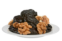 Dry prune and walnut. Dry prune fruit and walnut on plate Royalty Free Stock Photography