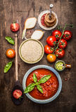 Dry Quinoa in ceramic bowl with tomatoes sauce and fresh ingredients for cooking, top view. Royalty Free Stock Image