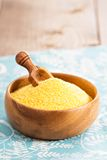Dry raw cornmeal in wooden bowl Stock Photo