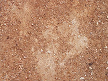 Dry red clay with stones textured background Stock Photos