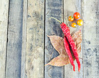 Dry red hot chili peppers and tomatos on wooden table Stock Photos