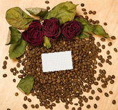 Dry red roses and blank paper sheet on coffee seeds and wooden background Stock Photos