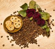 Dry red roses and cookies on coffee seeds and wooden background Stock Photos