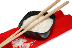 Dry rice in black bowl with chopsticks. On red cloth with white background Stock Photo