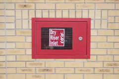 Dry riser inlet box red on brick wall for emergency fire services water connection for hose brigade engine at shopping mall retail. Park uk Stock Photography