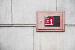 Dry riser inlet box red on brick wall for emergency fire services water connection for hose brigade engine at shopping mall retail stock photography