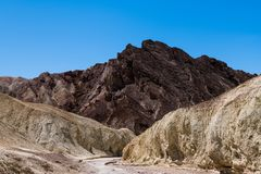 A dry riverbed cuts a pathway through a colorful desert canyon landscape to a rugged mountain peak stock images
