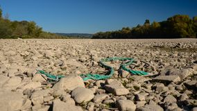 Dry riverbed on a nice autumn day with visible trees and broken turquoise rope. royalty free stock photos