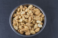 Dry roasted peanuts in metal bowl  on slate. Stock Photos