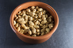 Dry roasted peanuts in terracotta  ramekin on slate. Royalty Free Stock Photos