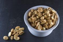 Dry roasted peanuts in white ramekin on slate. Bowl of dry roast peanuts on slate mat, some on slate royalty free stock photos