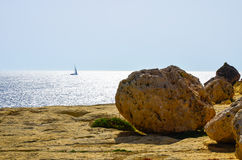 Dry rocky beach and a sailboat on the Mediterranean Sea. Scenic view of rocks and a dinghy on the Maltese Islands Stock Images