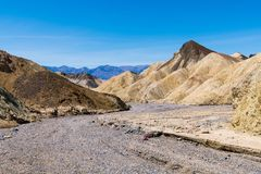 A dry rocky riverbed curves through a barren desert landscape of colorful badlands and peaks royalty free stock photography
