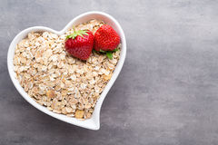 Dry rolled oatmeal in bowl. Royalty Free Stock Image