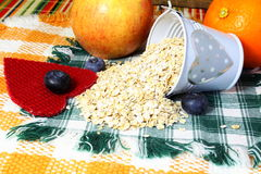 Dry rolled oatmeal flakes  in heart bucket with blueberry apple orange and heart Royalty Free Stock Photography