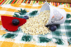 Dry rolled oatmeal flakes  in heart bucket with blueberry and heart Royalty Free Stock Image
