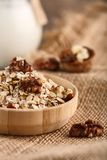 Dry rolled oatmeal in wooden bowl on textile background. Royalty Free Stock Image