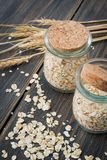 Dry rolled oats or oat flakes in craft glass jars with oat spike Royalty Free Stock Photo