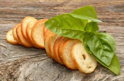Dry rolls bread and basil on wooden background. In studio royalty free stock image