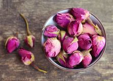 Free Dry Rose Buds Flowers In A Bowl On Old Wooden Table.Healthy Herbal Drinks Concept.Asian Ingredient For Aromatherapy Tea. Royalty Free Stock Image - 113035716