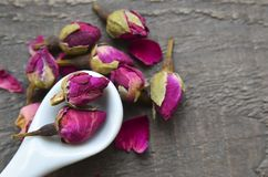 Dry rose buds flowers in a white spoon on old wooden table.Asian ingredient for aromatherapy herbal tea. royalty free stock images