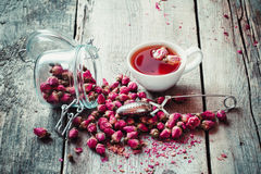Dry rose buds, tea cup, strainer and glass jar with rosebuds. Stock Photos
