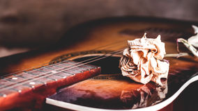 Dry rose flower on the strings of a guitar