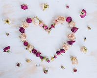 Dry rose flowers in heart shape on old wooden background Royalty Free Stock Photo