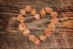 Dry rose flowers heart on wood panel Royalty Free Stock Image
