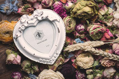 Dry rose flowers heart on wood panel Royalty Free Stock Images