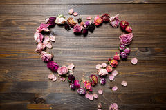 Dry rose flowers heart on wood panel. Stock Images