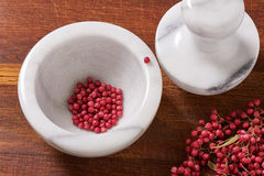 Dry rose pepper in white marble mortar next pestle Stock Photos