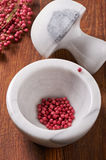 Dry rose pepper in white marble mortar next pestle Royalty Free Stock Photography