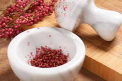 Dry rose pepper in white marble mortar next pestle Royalty Free Stock Photos