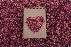 Dry petals form a heart shape  on a spiral notebook. Dry rose petals form a heart shape  on a spiral notebook Stock Images