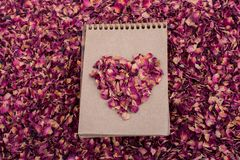 Dry petals form a heart shape  on a spiral notebook. Dry rose petals form a heart shape  on a spiral notebook Royalty Free Stock Image