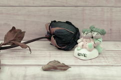 Dry roses and ceramic doll on wood pattern background with color Stock Photography