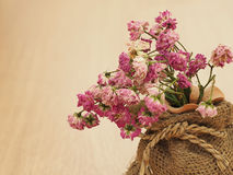 Dry roses, dried roses, blurred dry pink roses in brown sack on wood floor, vintage roses, concept of love Stock Photography