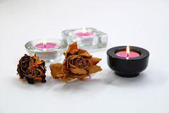 Dry roses and glass candlesticks. Dry roses and black and transparent glass candlesticks Stock Images